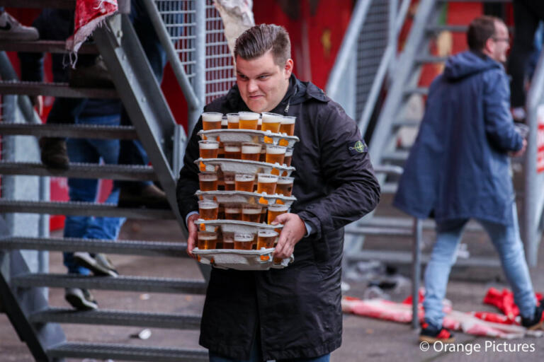 Een supporter van FC Twente sleept met een hele lading bier
